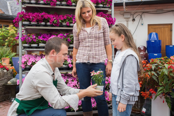 Garden center worker giving a flower to child while her mother standing next to her Stock photo © wavebreak_media