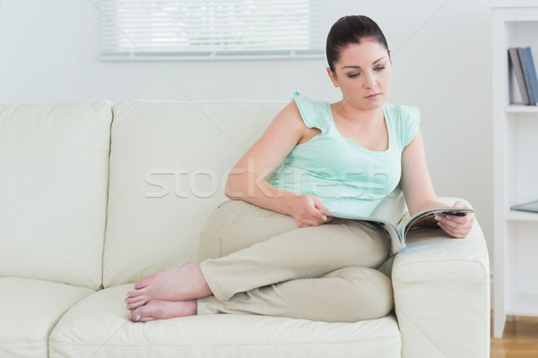 Woman relaxing on sofa with magazine in living room Stock photo © wavebreak_media