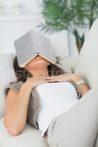 Brunette lying on sofa and sleeping with her book on the head in the living room Stock photo © wavebreak_media