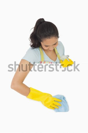 Smiling woman in rubber gloves and apron pointing on white surface Stock photo © wavebreak_media