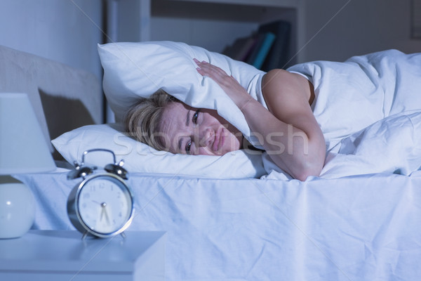 Woman covering ears with pillow as alarm clock rings Stock photo © wavebreak_media