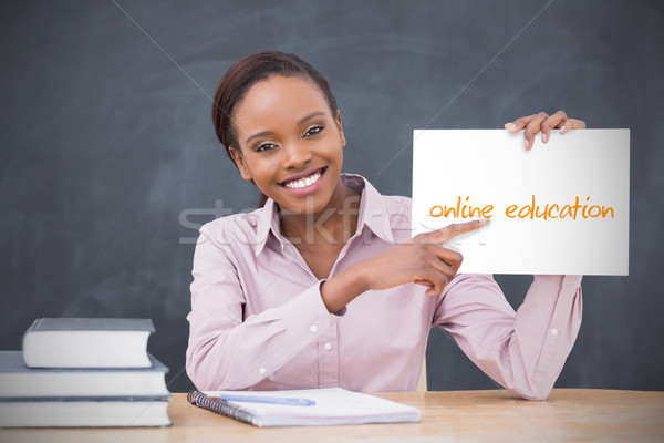 Happy teacher holding page showing online education Stock photo © wavebreak_media