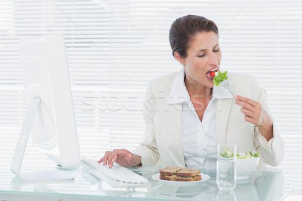 üzletasszony eszik saláta számítógéphasználat asztal fiatal Stock fotó © wavebreak_media
