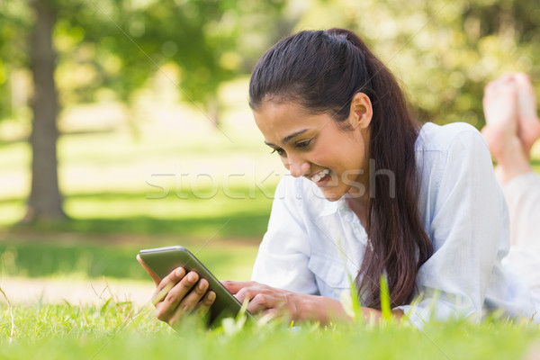 Woman text messaging while relaxing in park Stock photo © wavebreak_media