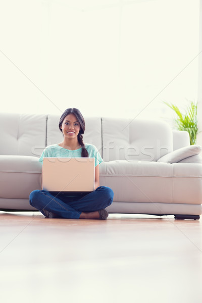 Pretty girl sitting on floor using her laptop smiling at camera Stock photo © wavebreak_media