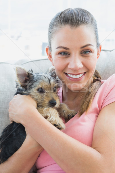 Smiling woman cuddling her yorkshire terrier on the couch Stock photo © wavebreak_media