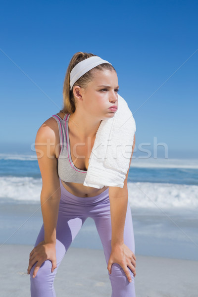 Sporty blonde standing on the beach with towel Stock photo © wavebreak_media