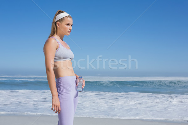 Sporty blonde standing on the beach with water bottle Stock photo © wavebreak_media