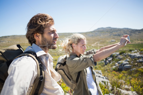 Hiking couple standing on mountain terrain taking a selfie Stock photo © wavebreak_media