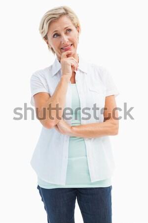 Happy mature blonde thinking with hand on chin Stock photo © wavebreak_media