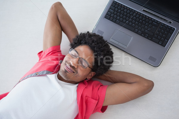 Businessman napping on floor near laptop Stock photo © wavebreak_media