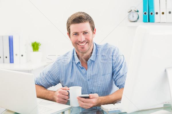 Sorridere imprenditore mug telefono ufficio Foto d'archivio © wavebreak_media
