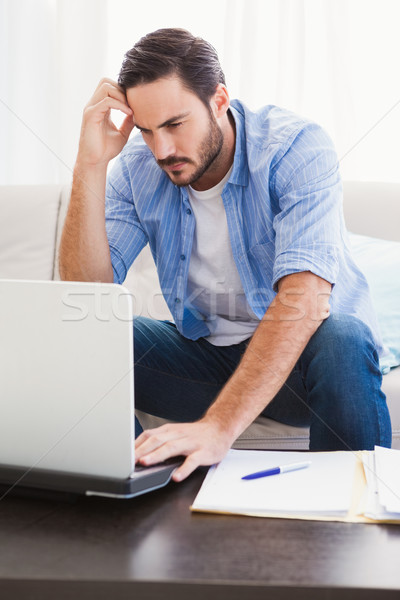 Worried man sitting at table using laptop to pay his bills Stock photo © wavebreak_media