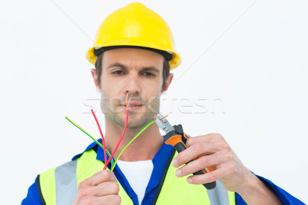 Handsome electrician cutting wire with pliers Stock photo © wavebreak_media