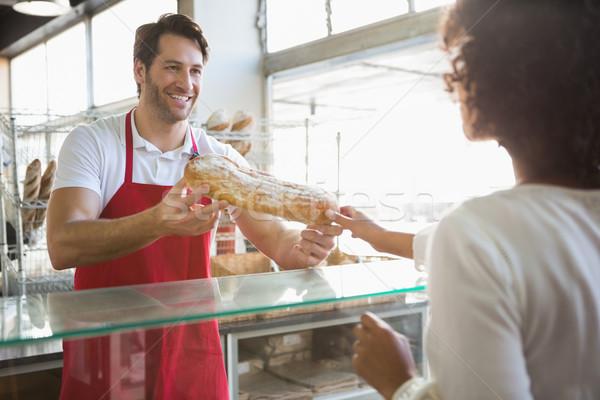 Sonriendo Baker pan transacción cliente panadería Foto stock © wavebreak_media