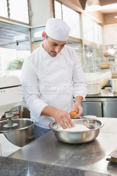 Baker cracking eggs on flour Stock photo © wavebreak_media