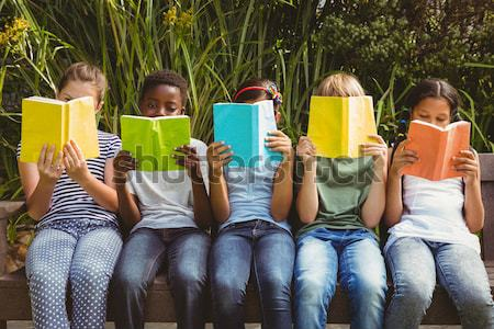 Composite image of children reading books at park Stock photo © wavebreak_media