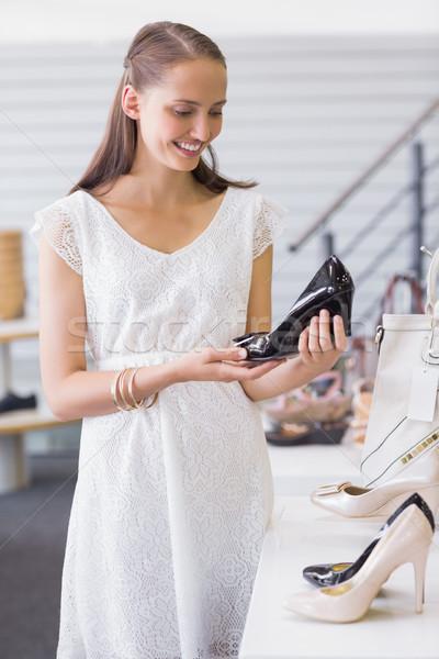 Pretty brunette looking at a heel shoe Stock photo © wavebreak_media