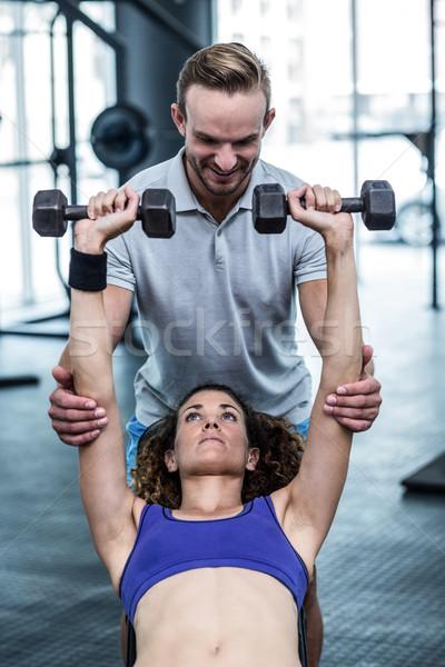 A muscular woman lifting dumbbells Stock photo © wavebreak_media