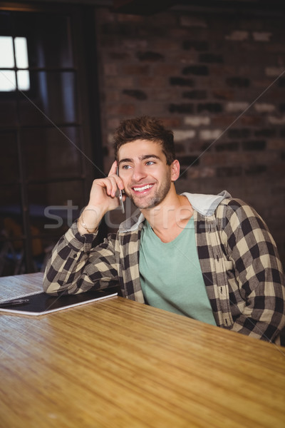 Smiling hipster phoning with smartphone Stock photo © wavebreak_media