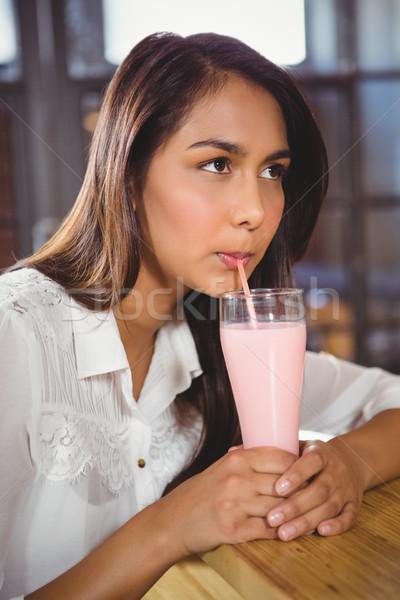 A beautiful woman drinking a pink milkshake Stock photo © wavebreak_media
