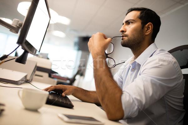 Figyelmes üzletember számítógéphasználat irodai asztal kép asztal Stock fotó © wavebreak_media