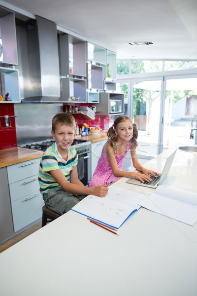 Portrait of smiling siblings doing their homework in kitchen Stock photo © wavebreak_media