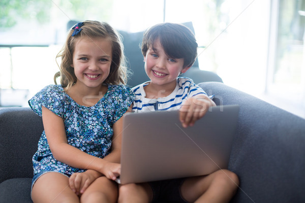 Smiling siblings using laptop in living room Stock photo © wavebreak_media