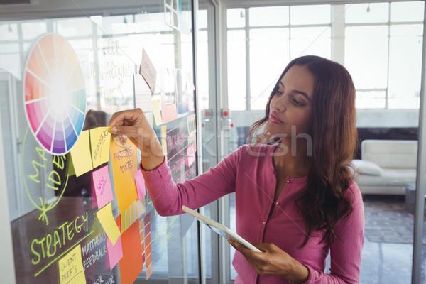Vrouwelijke ontwerper zelfklevend merkt glas Stockfoto © wavebreak_media