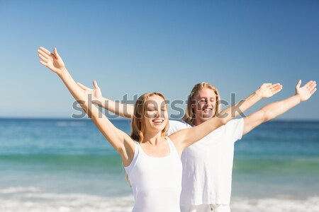Couple with arms outstretched exercising at beach Stock photo © wavebreak_media