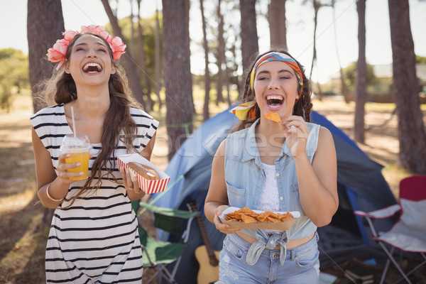 Happy friends eating snacks while camping in forest Stock photo © wavebreak_media