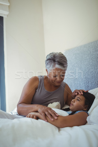 Grandmother comforting sick granddaughter in bed room Stock photo © wavebreak_media
