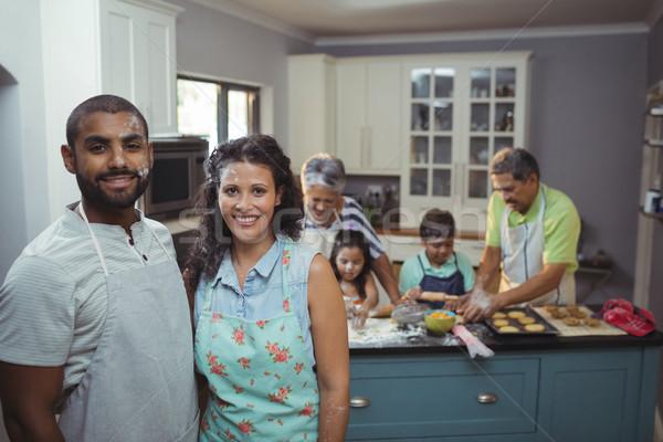 Couple smiling at camera while family members preparing dessert in background Stock photo © wavebreak_media