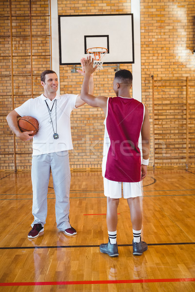 Coach high fiving with basketball player Stock photo © wavebreak_media