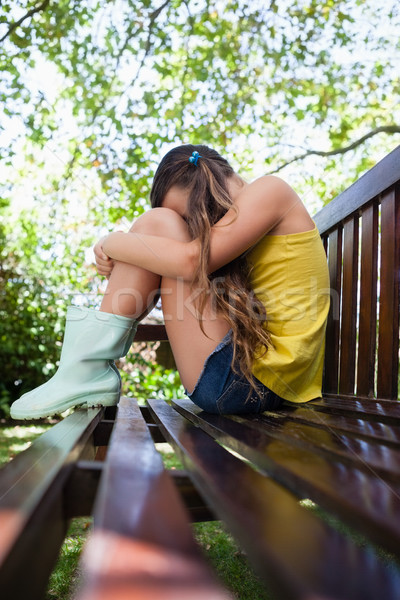 Side view of sad girl sitting on wooden bench Stock photo © wavebreak_media