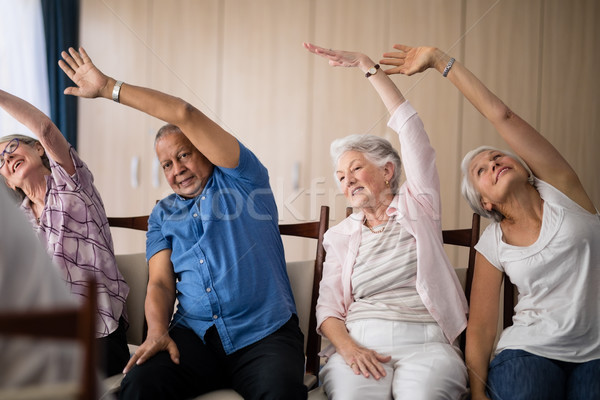 Senior people stretching while sitting on chairs Stock photo © wavebreak_media