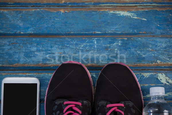 Overhead view of sports shoes amidst mobile phone and water bottle Stock photo © wavebreak_media