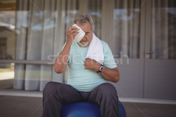 Senior man wiping sweat off his face with towel Stock photo © wavebreak_media