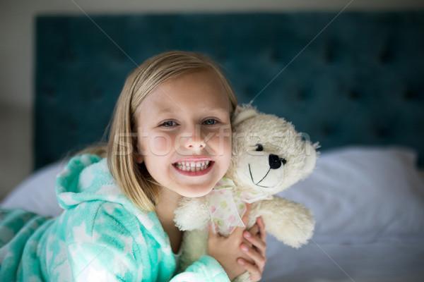 Sonriendo nina osito de peluche cama dormitorio Foto stock © wavebreak_media