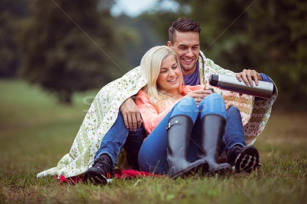 Happy couple sitting under blanket Stock photo © wavebreak_media