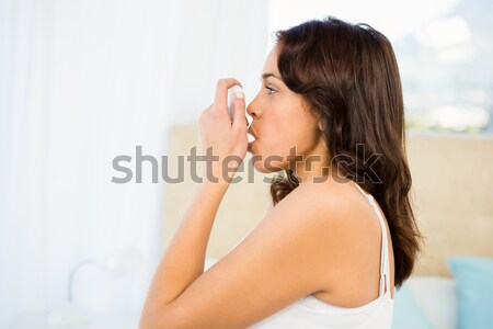 Side view of a woman using her inhaler Stock photo © wavebreak_media