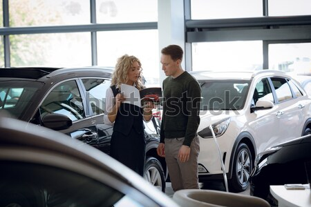 Salesman showing car to female customer in showroom Stock photo © wavebreak_media