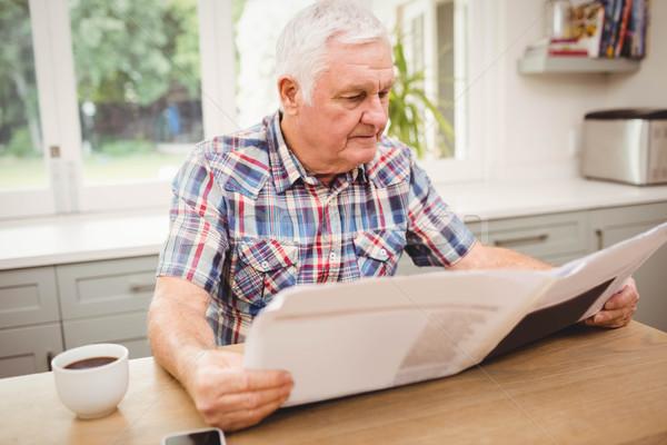 Stock photo: Senior man reading a newspaper