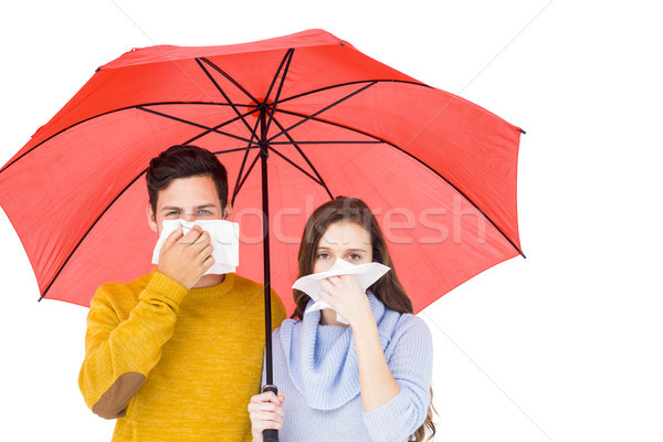 Stock photo: Couple blowing their noses under an umbrella