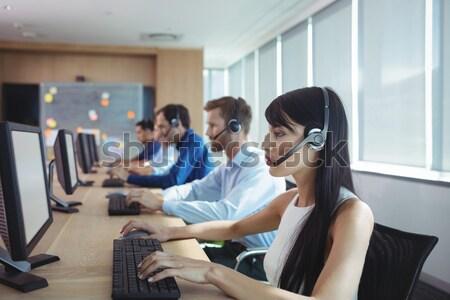 Female executive talking on phone while holding coffee mug Stock photo © wavebreak_media