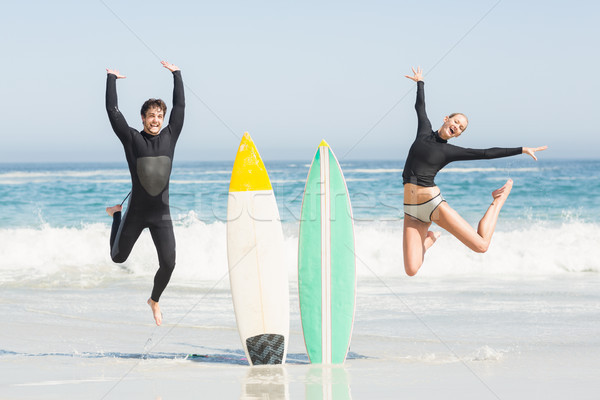 Excited couple jumping next to surfboards Stock photo © wavebreak_media