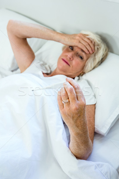 High angle view of aged woman checking thermometer Stock photo © wavebreak_media