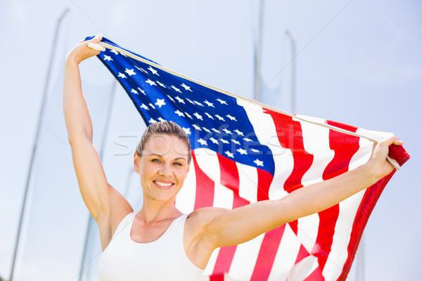Boldog női atléta magasra tart amerikai zászló stadion Stock fotó © wavebreak_media