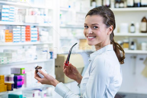 Pharmacist holding a medicine bottle in pharmacy Stock photo © wavebreak_media