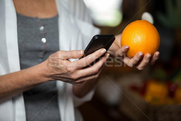 Stock photo: Mid section of female costumer holding orange while using mobile phone